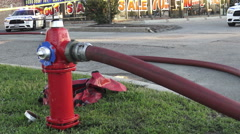 Red water hydrant on the street in use with fire hose attached, Canada Stock Footage