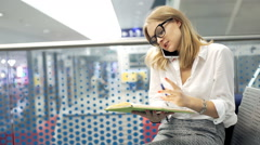 Businesswoman writes down the appointment while talking on cellphone Stock Footage