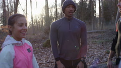 4K Happy friends enjoying a run in the woods stop to take a break & high five Stock Footage