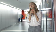 Businesswoman drinking coffee and smiling to the camera on hallway Stock Footage