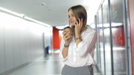Businesswoman chatting on cellphone while drinking coffee in hallway Stock Footage