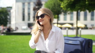 Happy businesswoman sitting outdoors and chatting on cellphone Stock Footage