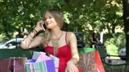 Girl looking excited while talking on cellphone about her shopping Stock Footage