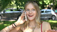 Beautiful girl sitting in the park and chatting on cellphone, steadycam shot Stock Footage