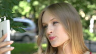 Pretty, blonde girl doing selfies on smartphone in the park Stock Footage
