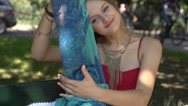 Happy girl putting news scarf while sitting in the park, slow motion shot  Stock Footage