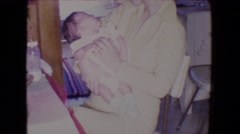 1961: mom comforting young baby while dad is very busy doing dishes in kitchen Stock Footage