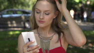 Pretty, stylish girl using smartphone in the park, slow motion shot Stock Footage