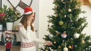 Pretty girl talking on the phone nearby Christmas tree Stock Footage