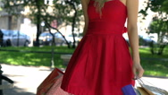 Attractive girl in red dress going round with shopping bags, slow motion shot at Stock Footage