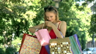 Excited girl standing with her shopping bags and looking on her new purchases Stock Footage