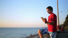 Young handsome man relaxing near the sea beach with tablet computer. He checks Stock Footage