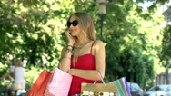 Beautiful, blonde girl holding shopping bags and chatting on cellphone Stock Footage