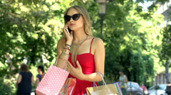 Irritated girl arguing through cellphone while standing with shopping bags Stock Footage