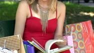 Stylish girl in red dress reading her journal on the bench Stock Footage