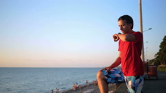 Young handsome man relaxing near the sea beach with smart watch. He checks Stock Footage