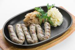 From turkey veal roasted with paprika sausages in black pan on wooden cutting Stock Photos