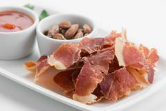 Spicy chips of ham with smoked almonds on white plate Stock Photos
