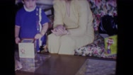 1961: child receiving gifts and playing with jack in box with family watching Stock Footage