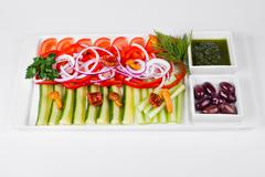 Assorted vegetables with sliced cucumber, tomatoes, chili, onion, olive and m Stock Photos