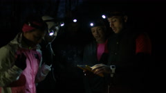 4K Group hiking in the woods at night using computer tablet for navigation Stock Footage