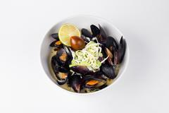 Blue mussels in a creamy sauce with lemon and olive in white bowl Stock Photos