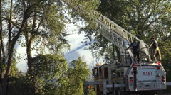 Two firemen on top of a fire truck with fire hose attached to a ladder platform  Stock Footage