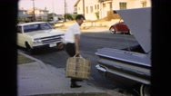 1966: man lifts box into trunk SAN PEDRO, CALIFORNIA Stock Footage