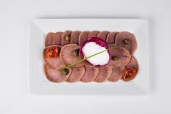 Beef tongue with horseradish and fried tomatoes on white plate background Stock Photos