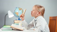 Portrait blonde school girl 7-8 years reading book sniffing and eating wafer Stock Footage