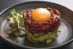 Avocado tartare stab Sakura beef meat with red egg and lettuce on black platt Stock Photos