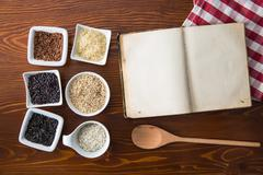 Blank cookbook and different rice varieties. Stock Photos