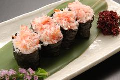 Red snow crab loosened kimbap on green leaf tray in restaurant Stock Photos