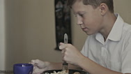 Close-up portrait of a schoolboy eating spaghetti Stock Footage