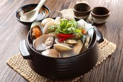 Black stew of Jogaetang clam soup with chili and cumin herbs on wooden korean Stock Photos