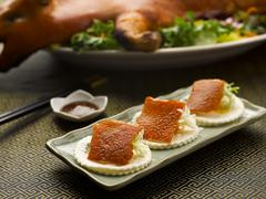 Roasted Suckling Pig skin with onion and crackers on dish in restaurant Stock Photos