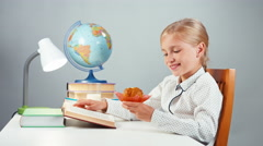 School girl 7-8 years reading book and eating muffin Stock Footage