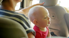 Mom goes with the kid in the back seat of the car. Cute little boy 1 year old Stock Footage