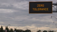 Zero tolerance distracted and texting driving police warning sign over highway Stock Footage
