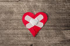 Wounded heart with plaster Stock Photos