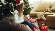 Young beautiful girl wraps a Christmas gift Stock Footage