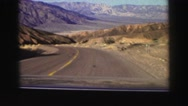 1969: view from car driving down desert road near mountains YOSEMITE, CALIFORNIA Stock Footage