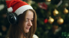 Pretty brunette in Christmas cap listen to the music and sing Stock Footage