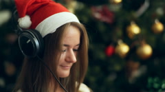Pretty brunette in Christmas cap listen to the music Stock Footage