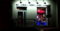Barber, luminous night window hairdresser cuts client Stock Footage