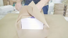 Close up man's hands packing boxes of sellotape in printing industry, front view Stock Footage
