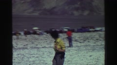 1969: people stand on salt flat below mountain next to cars YOSEMITE, CALIFORNIA Stock Footage