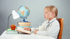 School girl 7-8 years reading book drinking milk and smiling at camera isolated Stock Footage