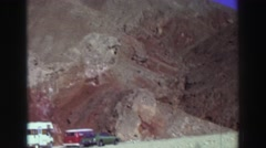 1969: cars parked under sunny mountain, person walks toward shadowy cleft Stock Footage