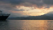 Large ship sailing into the port at sunrise over the ocean. Mountains and orange Stock Footage
